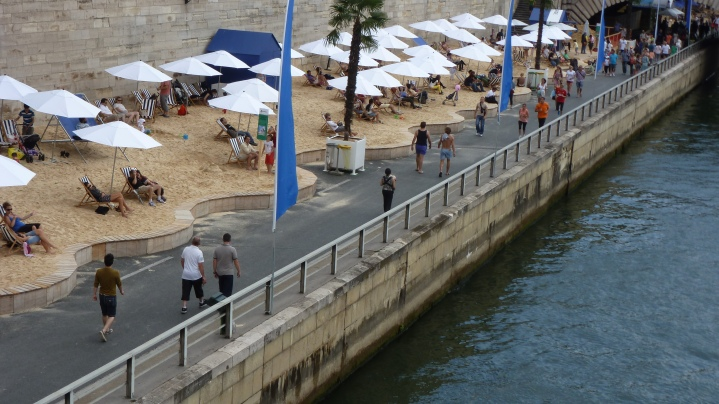Paris Plages (beaches) overtake the roadways along River Seine during summer months