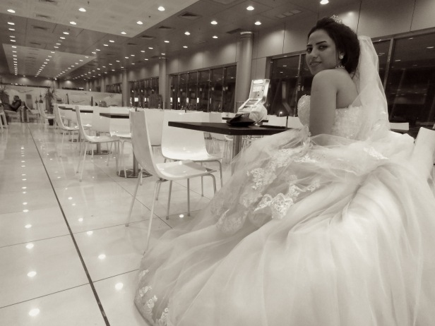 An Egyptian Bride waits for her new husband at the Kuwait airport, fully dressed in white wedding gown and veil