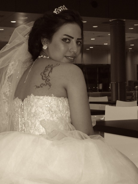 An Egyptian Bride waits for her new husband at the Kuwait airport, fully dressed in white wedding gown and veil. Here she shows off her butterfly tattoo