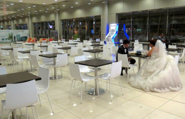 An Egyptian Bride waits for her new husband at the Kuwait airport, fully dressed in white wedding gown and veil. Here, her groom made an appearance. The two met with a sincere kiss and settled down to exchange stories. In the airport cafe.