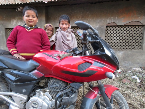 Schoolchildren proudly pose for a photo with their father's red motorcycle in Kathmandu, Nepal. Read their story at www.beautifulfillment.com