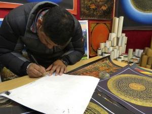 A Mandala Artist signs his original works in his shop at Durbar Square in Kathmandu, Nepal. Read his story at www.beautifulfillment.com