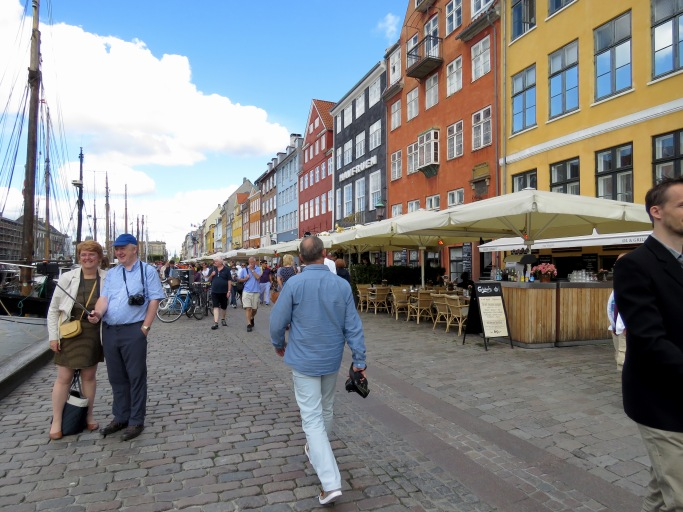 Tourists stop for selfies and locals casually stroll past colorful shops along the Nyhavn Canal in Copenhagen, Denmark - Read about the sites and activities in Copenhagen at www.beautifulfillment.com