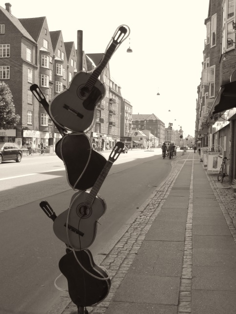 A shop's creative guitar sculpture is displayed on the streets of Copenhagen  -  Read about the sites and activities of Copenhagen, Denmark at www.beautifulfillment.com