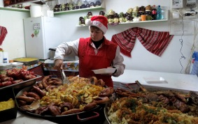 Hearty meals of meats and potatoes served at Bucharest's Christmas Market - Bucharest Romania - by Anika Mikkelson - Miss Maps - www.MissMaps.com