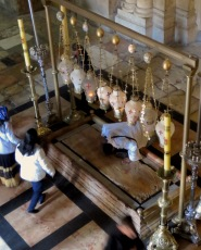 A man kneels in prayer at the Stone of the Anointing inside Church of the Holy Sepulchre - by Anika Mikkelson - Miss Maps - www.MissMaps.com