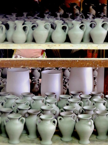 Mugs and Jugs sit on the shelves of Emira Pottery in Larnaca, Cyprus - by Anika Mikkelson - Miss Maps - www.MissMaps.com