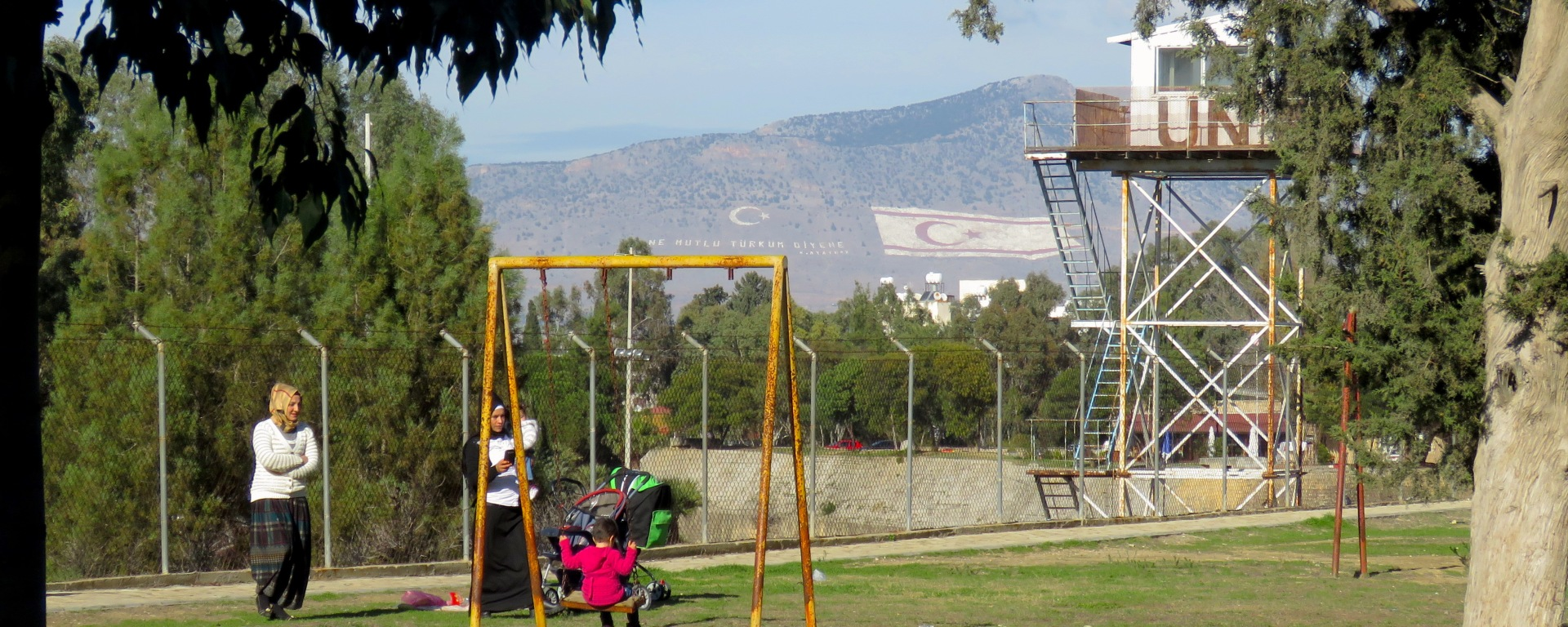 Two Turkish Cypriot Women and their children play in Nicosia's Forbidden Zone with two stark reminders of the occupation on nearby mountains - by Anika Mikkelson - Miss Maps - www.MissMaps.com