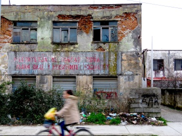 Abandoned Building and Biciklist - Shkoder Albania - by Anika Mikkelson - Miss Maps - www.MissMaps.com