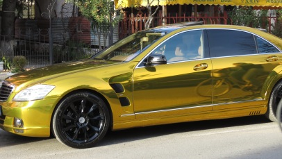 Gold S-Class Mercedes shines enough to reflect a cyclist riding by - Shkoder Albania - by Anika Mikkelson - Miss Maps - www.MissMaps.com