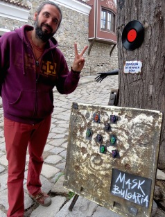 Masks of Bulgaria - this guy sells necklaces and asks customers to take photos of them around the world Plovdiv, Bulgaria - by Anika Mikkelson - Miss Maps