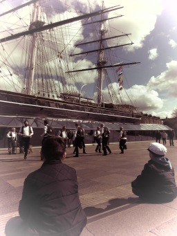 Two boys watch performances by the Blackheath Morris Men and Cutty Shark Ship in Greenwich London UK - by Anika Mikkelson - Miss Maps