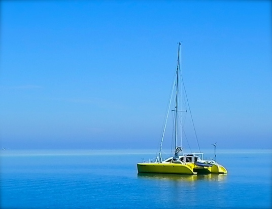 A Fijian shot of a boat called Citrus Tart - see how the sea melts into the sky - by Kirsty Mullahy - MissMaps.com Featured Female Traveler