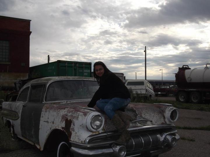 "Samita At a small-town car dump in Melville, Ontario, when she took VIA rail's train route ""The Canadian"" across the country - by Samita Sarkar - Miss Maps Featured Female Traveler"