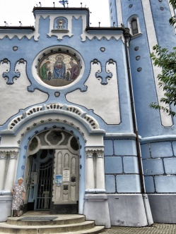 A woman stands outside the Blue Church of Bratislava Slovakia - by Anika Mikkelson - Miss Maps - www.MissMaps.com