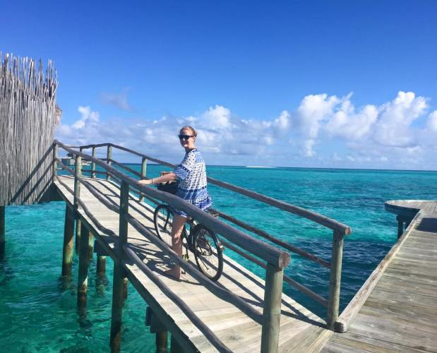 Sally riding her personalised bike to her overwater villa in The Maldives - MissMaps.com Featured Female Traveler