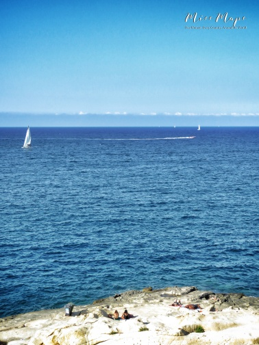 Down by the bay - sunbathers and sailboats - Malta - by Anika Mikkelson - Miss Maps - www.MissMaps.com