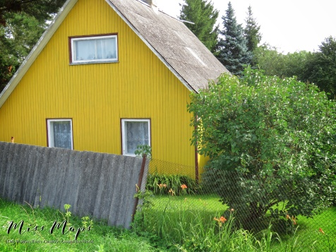 This sweet yellow house looks is the first in the town - Northern Estonia - by Anika Mikkelson - Miss Maps - www.MissMaps.com
