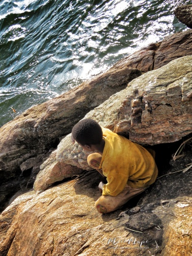 Boy Watching Fishermen on the Nile River - Jinja Uganda - by Anika Mikkelson - Miss Maps - www.MissMaps.com