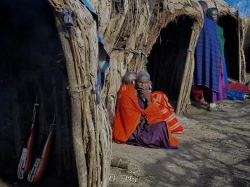Maasai Woman Outside Huts- Tanzania - by Anika Mikkelson - Miss Maps - www.MissMaps.com